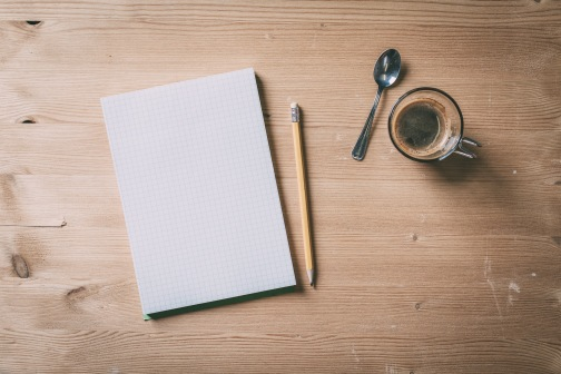 Paper notebook with pencil and coffee on a wood table